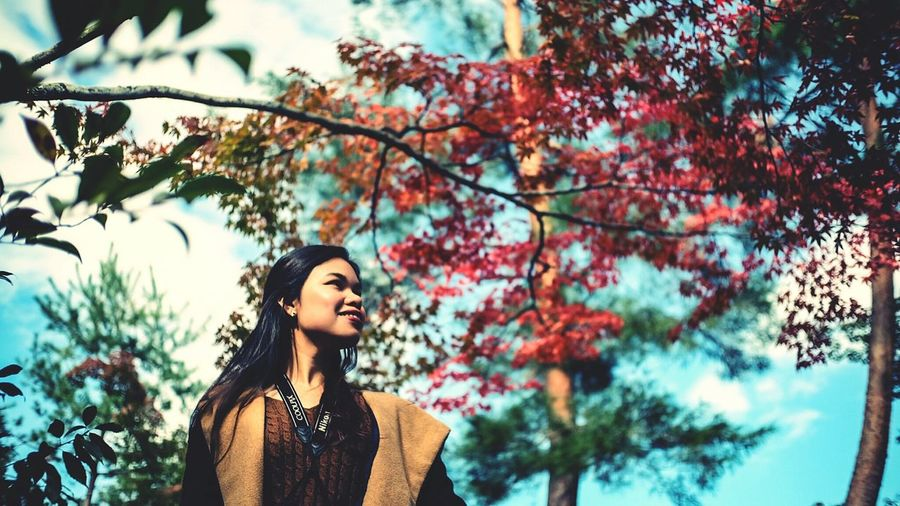 Low Angle View Of Woman Looking Away Against Trees
