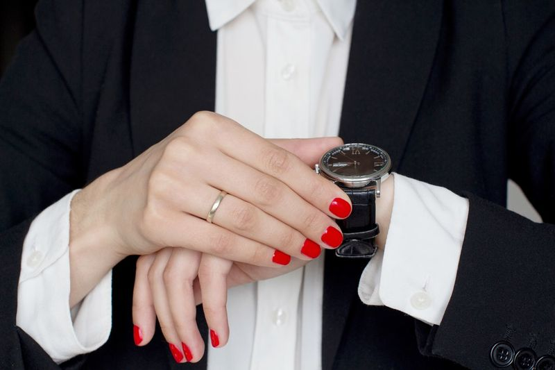 Young woman in black suit with red manicure on nails checking time Business Person Work Time Wristwatch Black And White Suit Office Menswear Boss Stylish Busy Working Hard Classical Style Power Strongwoman Business Woman Business Meeting Manager Nail Polish Midsection Nail Women Hand Adult Red Nail Polish Jewelry Ring Lifestyles Fashion Red