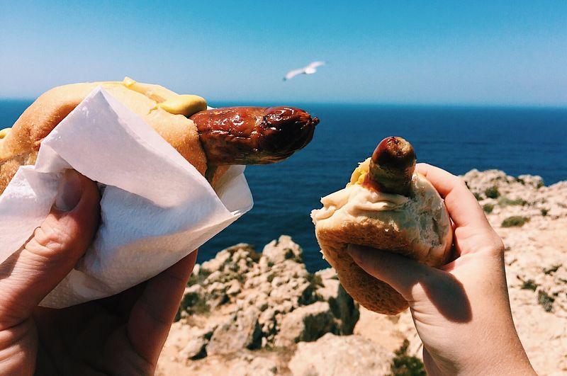 Cropped hand holding coburger bratwurst against sea