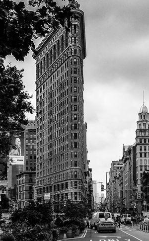 Flatiron in Black and White Flatiron Building I Love New York Mid Day Sun And Clouds NYC Photography NYC Street Photography Architecture Building Exterior Built Structure Car City City Street Commute Day Land Vehicle Low Angle View Mode Of Transport No People Outdoors Road Sky Skyscraper Street Transportation Travel Destinations Tree