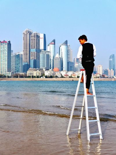 Qingdao Qingdao China Beach Photography Qingdao Seaside Wedding Photography Fotograf Skyscraper City Architecture Built Structure One Person Standing Building Exterior Clear Sky Urban Skyline Water Ladder Ladder In Sky Ladder Into Happiness The Street Photographer - 2017 EyeEm Awards Qingdao