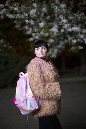 Woman wearing fur coat while looking away outdoors