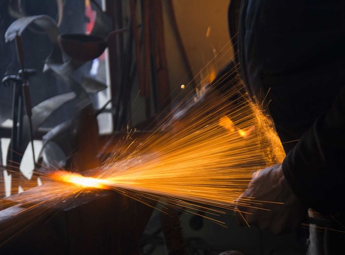 Sparks Emitting From Metal While Worker Working In Industry