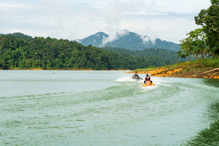 People enjoying water activities on banana boat at the kenyir lake, terengganu, malaysia.
