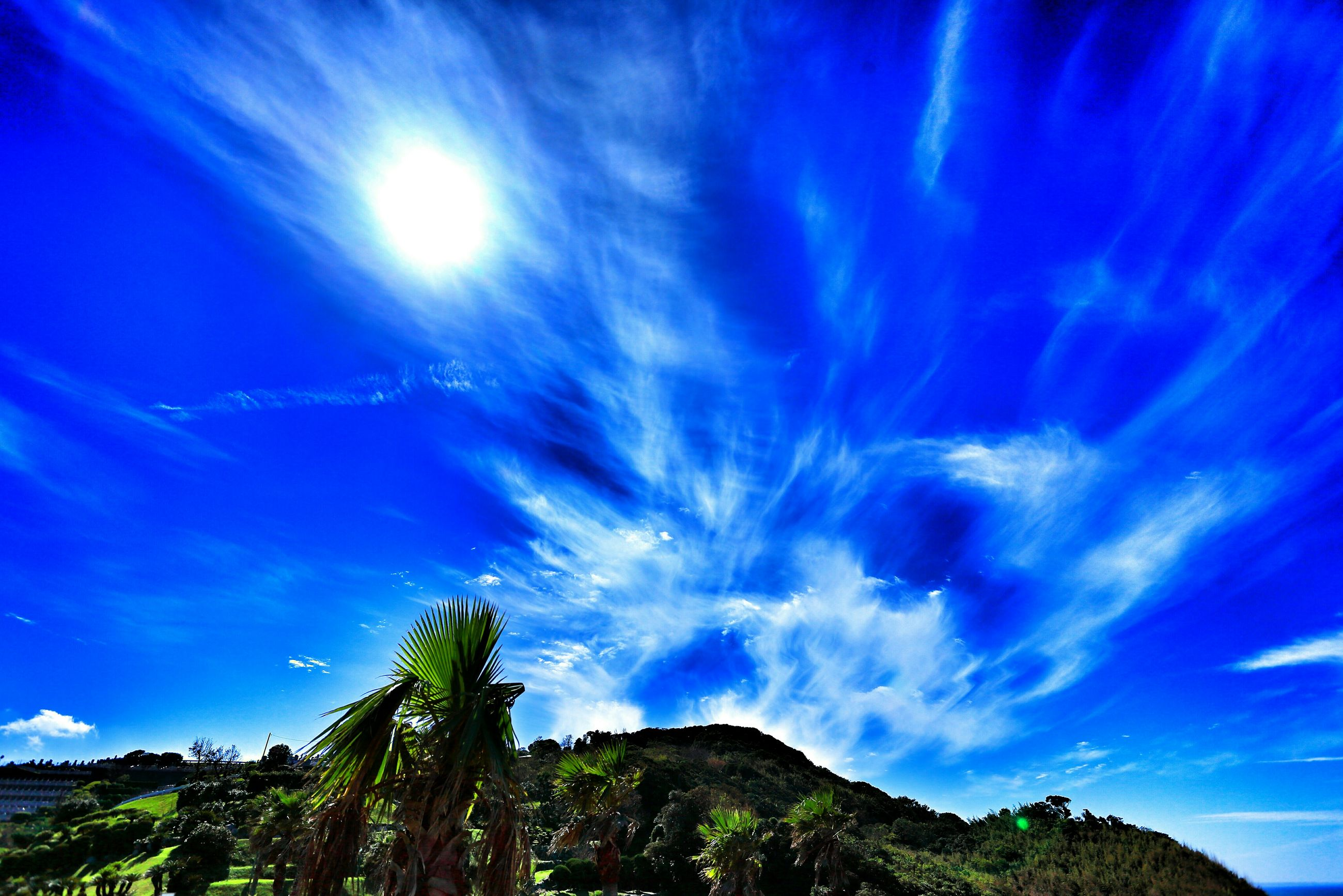 blue, tranquility, sky, tranquil scene, beauty in nature, scenics, sunlight, low angle view, nature, sunbeam, sun, cloud - sky, tree, mountain, idyllic, cloud, landscape, lens flare, non-urban scene, day