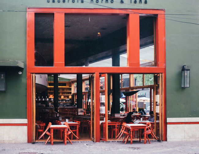 Chairs and tables at sidewalk cafe against buildings in city