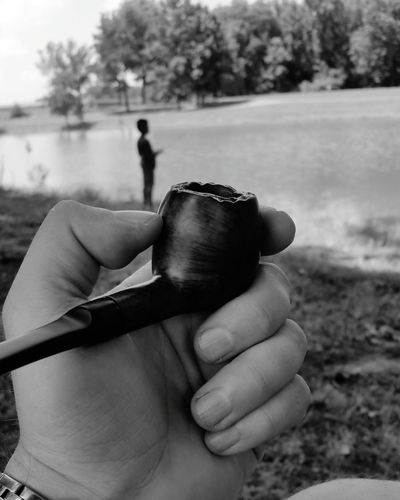 Cropped Image Of Person Holding Smoking Pipe Against River