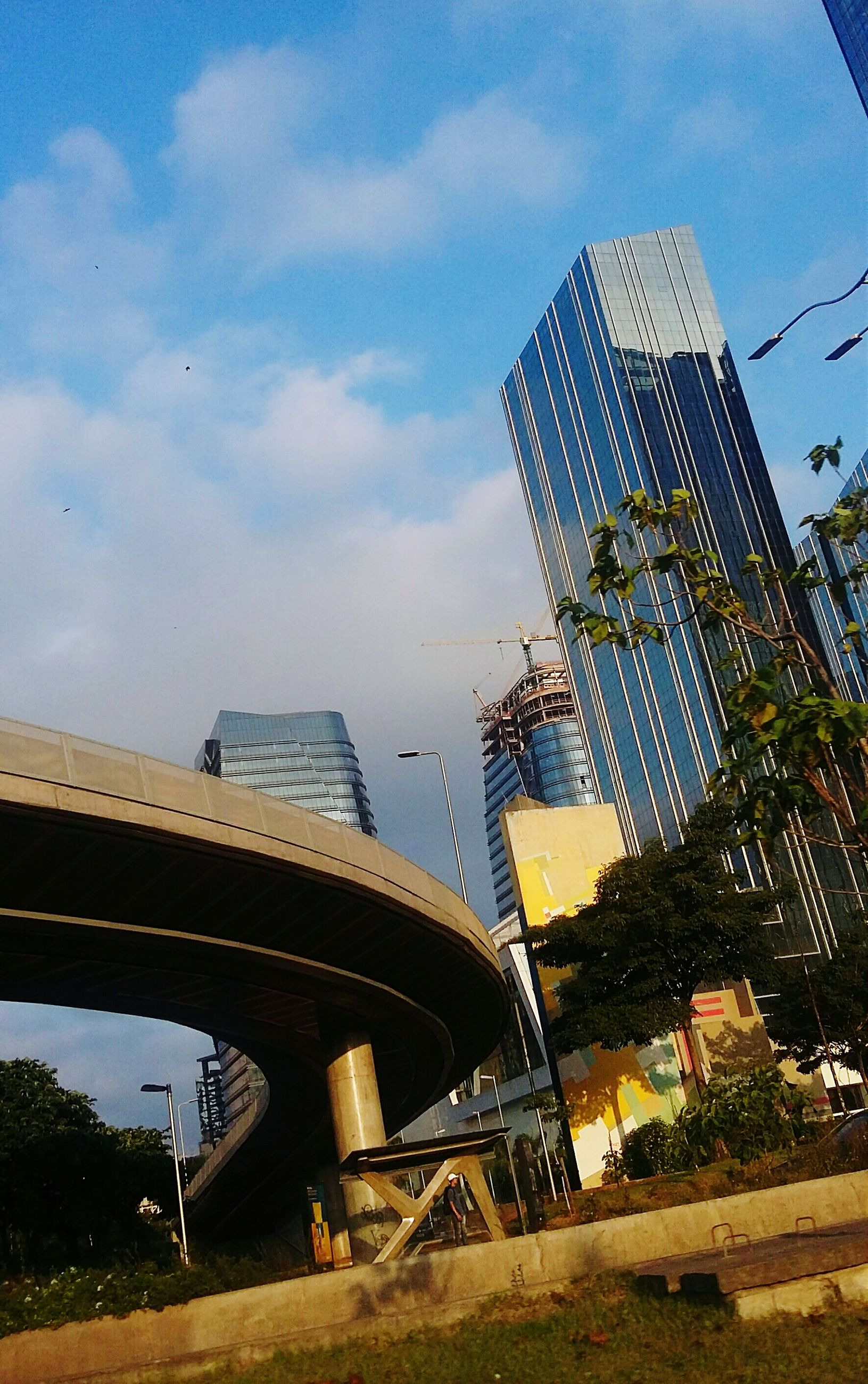 architecture, built structure, sky, building exterior, city, cloud - sky, low angle view, modern, tall - high, transportation, bridge - man made structure, tower, skyscraper, reflection, capital cities, travel destinations, cloud, travel, connection, office building