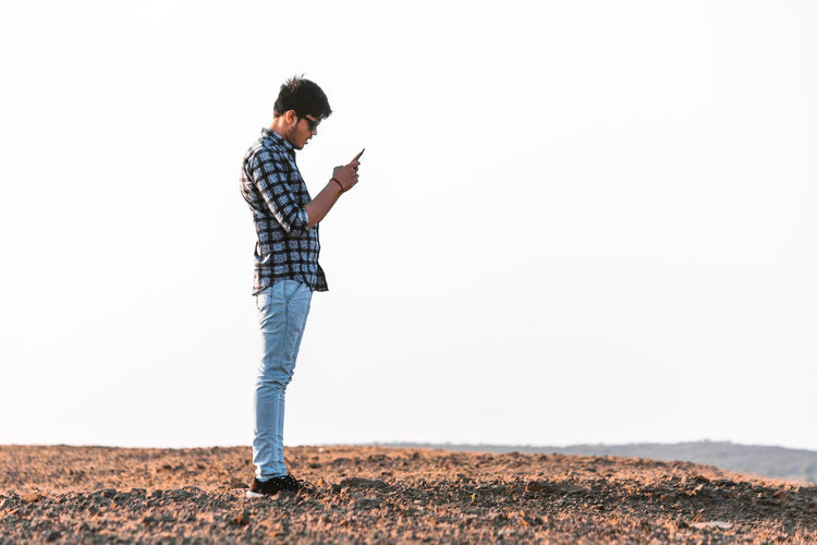 Casual Clothing One Person Copy Space Young Adult Standing Leisure Activity Full Length Sky Side View Technology Wireless Technology Lifestyles Clear Sky Real People Mobile Phone Nature Portable Information Device Communication Day Outdoors