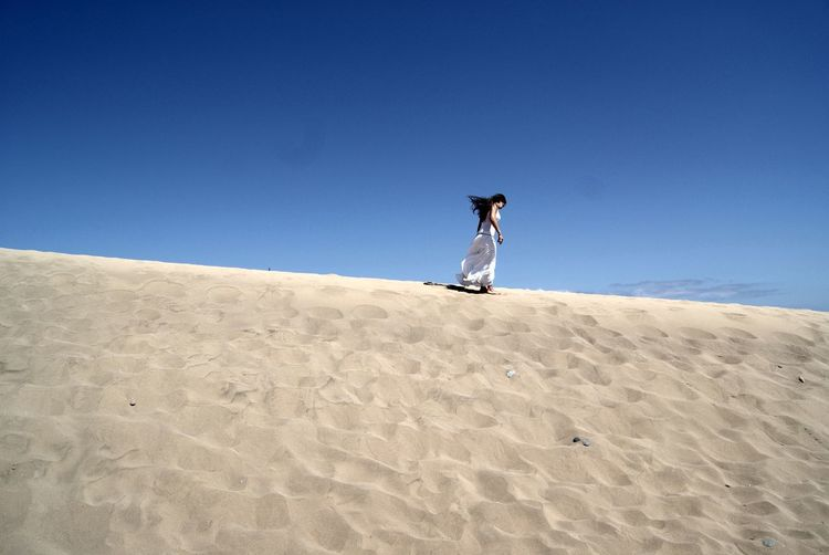 Low angle view of woman walking on sand dune at beach against clear blue sky