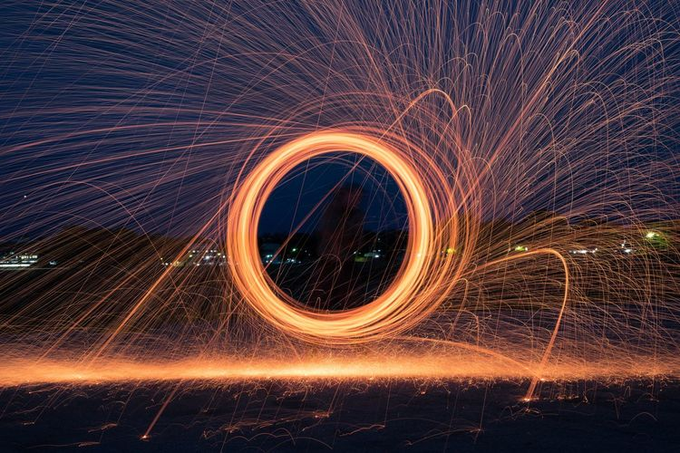 Wire wool spinning against sky at night