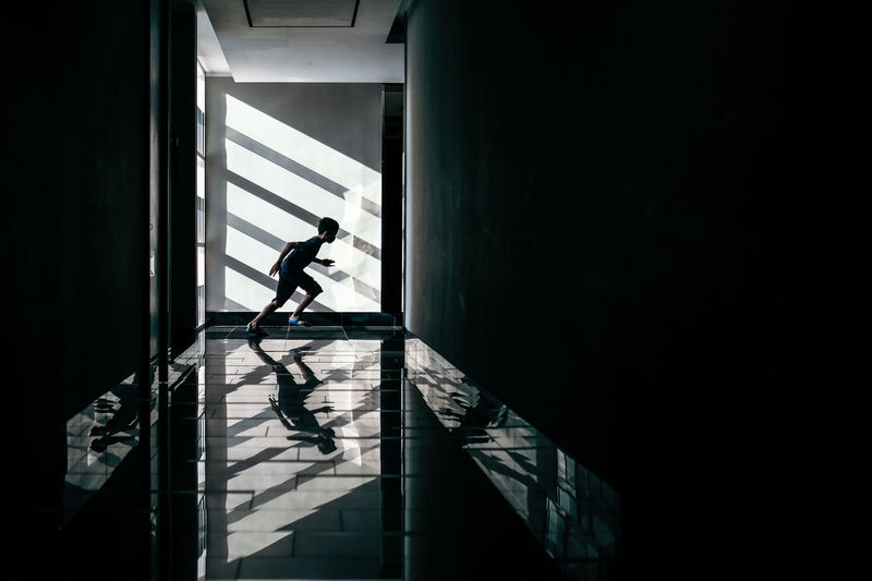 Side view of boy running in corridor