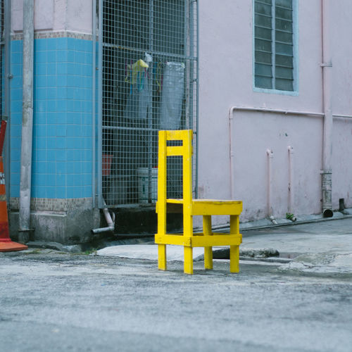 Yellow Wooden Chair On Footpath By Building