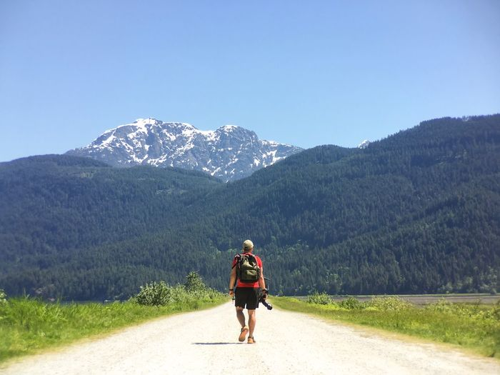 Rear view of man on road against mountain range