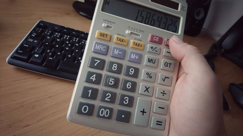 Calculator in hand. Office shot. Indoors  Table Human Hand Calculator Computer Keyboard Calculator Machine Office Business Hand