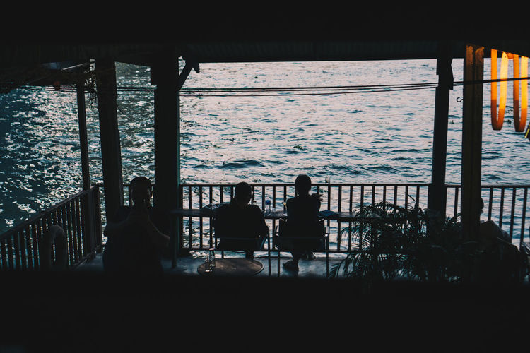 Sea Group Of People Water Silhouette Architecture Real People Sitting Lifestyles Built Structure Men Women Nature Railing People Adult Outdoors Leisure Activity Day Sky