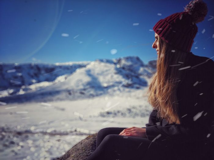 Side view of young woman sitting on snow covered field against blue sky