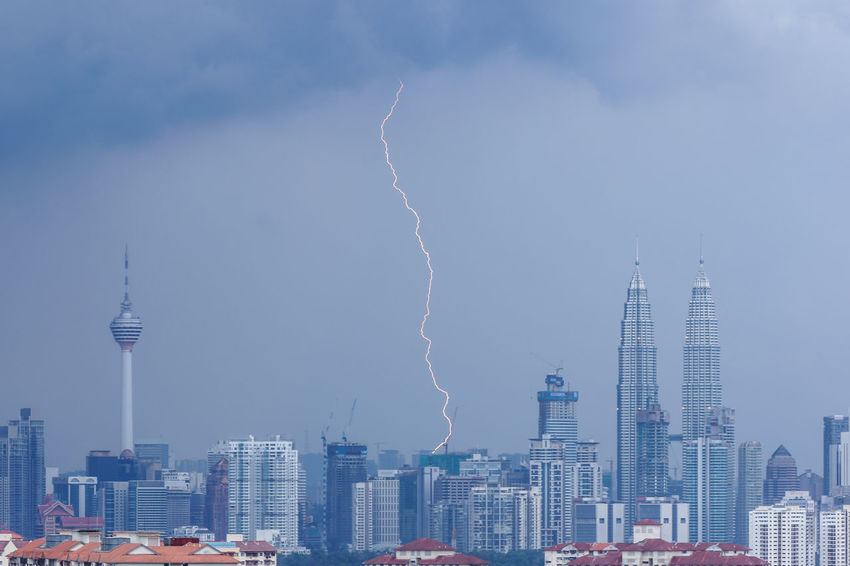 Lightning strike over downtown Kuala Lumpur, Malaysia. Architecture Building Exterior Building Story Built Structure City City Life Cityscape Communications Tower Development Environment Growth Modern Office Building Outdoors Power In Nature Scenics Sky Skyscraper Spire  Tall Tall - High Thunderstorm Tower Travel Destinations Urban Skyline