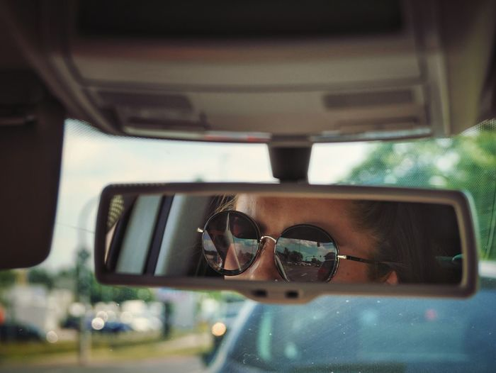Woman wearing sunglasses reflecting on rear-view mirror of car