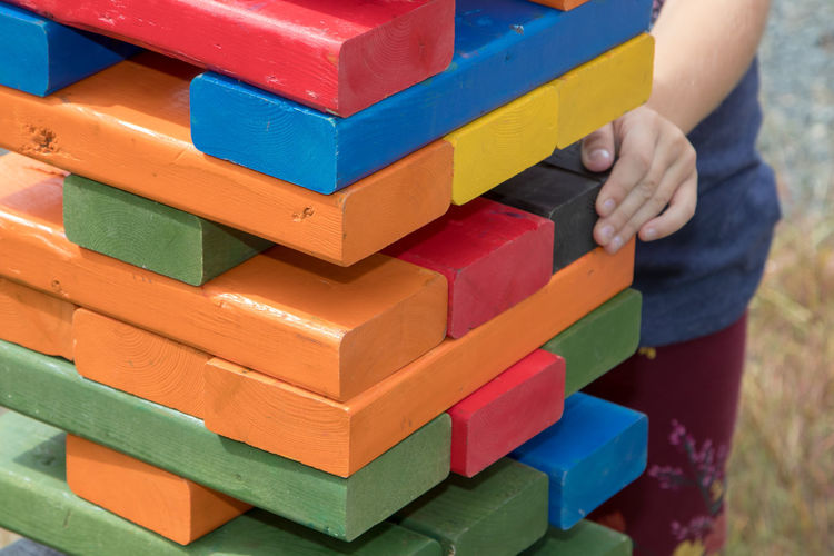 Cropped image of girl playing with colorful wooden blocks at playground