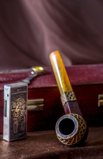 Close-up of smoking pipe and cigarette lighter by box on table