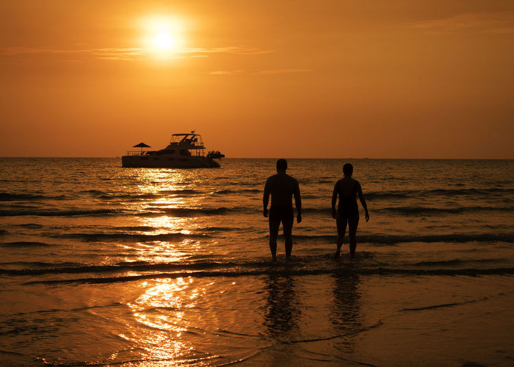 Silhouette people standing in sea against sky during sunset
