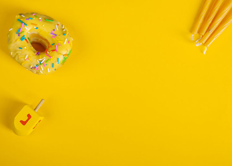 High angle view of multi colored pencils on yellow background