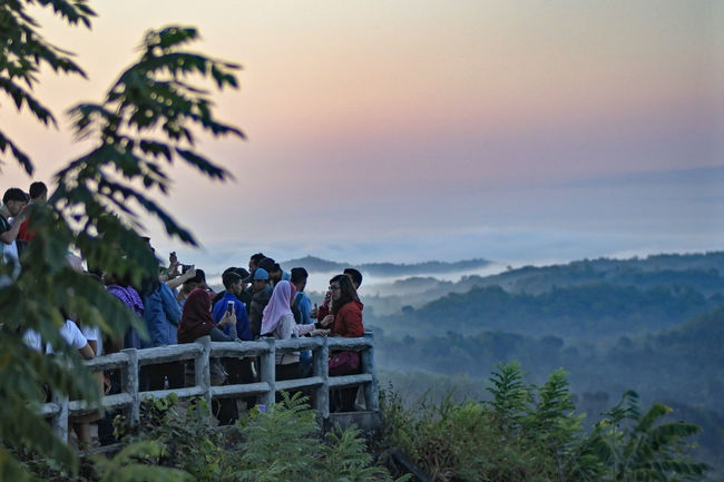 Conversation with Sunrise EyeEmNewHere EyeEm Nature Lover INDONESIA Yogyakarta Jogjakarta Sunrise Sunrise_Collection Sunrise Colors Mangunan Tree Togetherness Mountain Men Sky Landscape Hiking Backpack Mountain Climbing Adventure Explorer Climbing