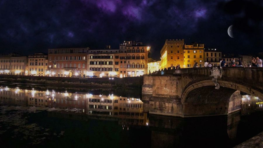 Arch bridge over river against buildings in city at night
