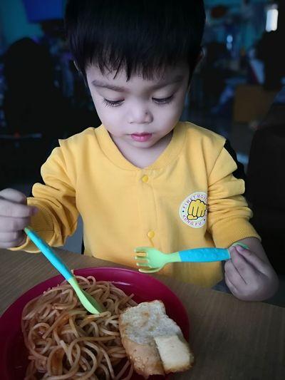 Boy holding ice cream on table