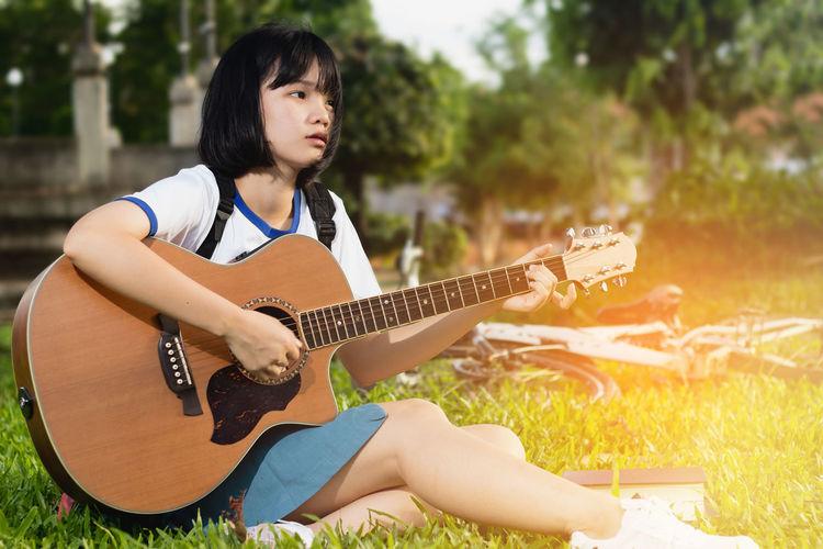 Teenage girl looking away while playing guitar on field