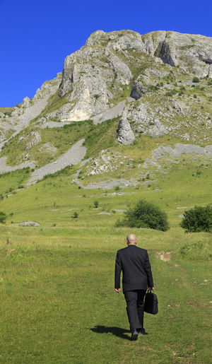 Businessman walking on grass near rocky mountains. Business Green Man Scenic Black Suit Businessman Concept Full Length Grass Landscape Mountain Nature One Man Only One Person Outdoors People Real People Rear View Scenics Strategy Suit Walking Well-dressed