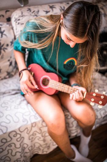 High angle view of woman playing ukulele