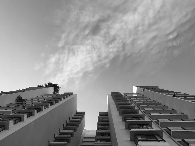 Looking up to the sky Black And White Blackandwhite Travel Destinations Tall - High Residential District City Outdoors Day Building Low Angle View Nature No People Cloud - Sky Built Structure Building Exterior Architecture Sky EyeEm Best Shots EyeEm Selects Sunlight In A Row Balcony Pattern Repetition Apartment Directly Below Roof Tile Roof