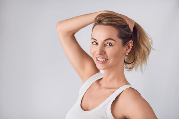 Attractive blond woman holding up her long hair Beautiful Copy Space Hair Happiness Happy Looking At Camera Woman Attractive Beauty Best Ager Blond Face Gray Background Holding Hair Up Middle-aged One Woman Only Portrait Studio Shot