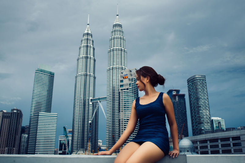 Woman sitting on retaining wall against petronas towers