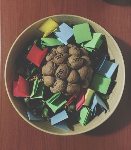 Directly Above Shot Of Colorful Papers With Walnuts In Bowl On Table