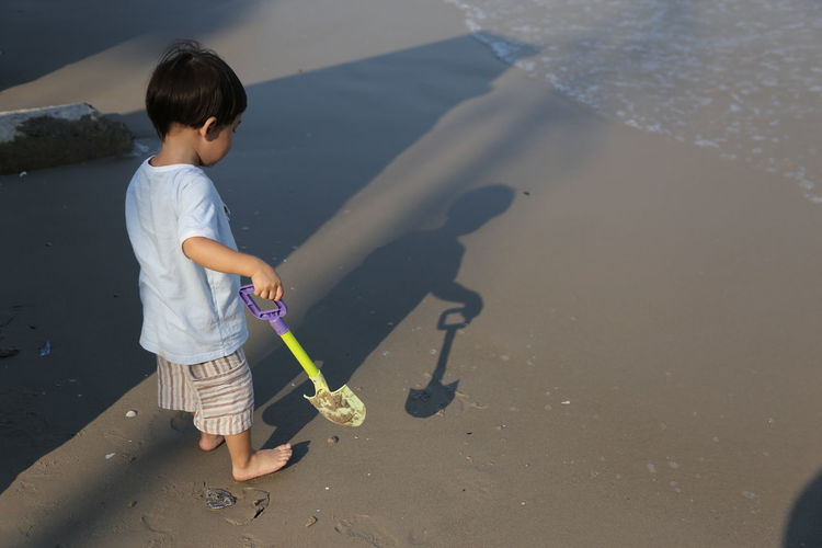 High angle view of boy with toy shovel at beach