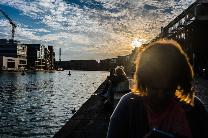 Woman photographing by river against sky during sunset