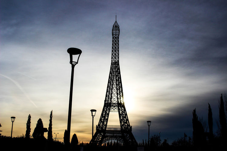 Low angle view of silhouette replica eiffel tower against sky during sunset
