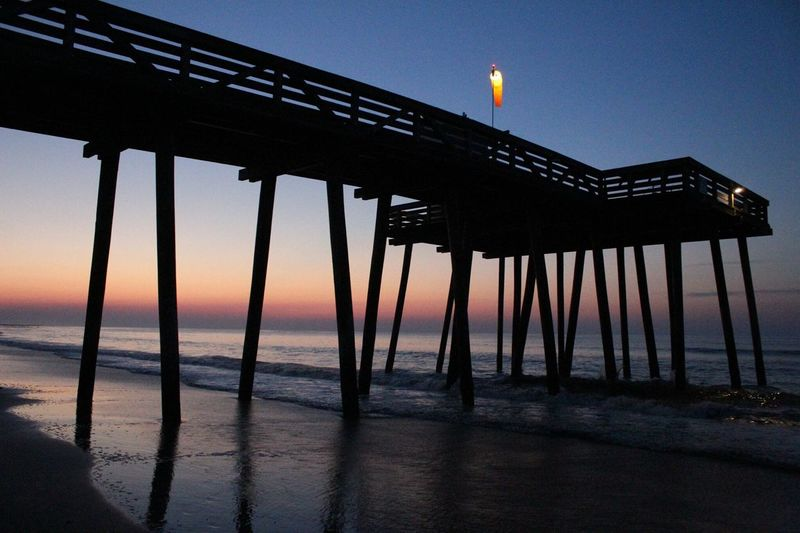 Low angle view of illuminated windsock on pier at beach during sunset