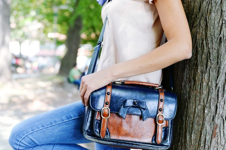 Midsection of woman with leather bag