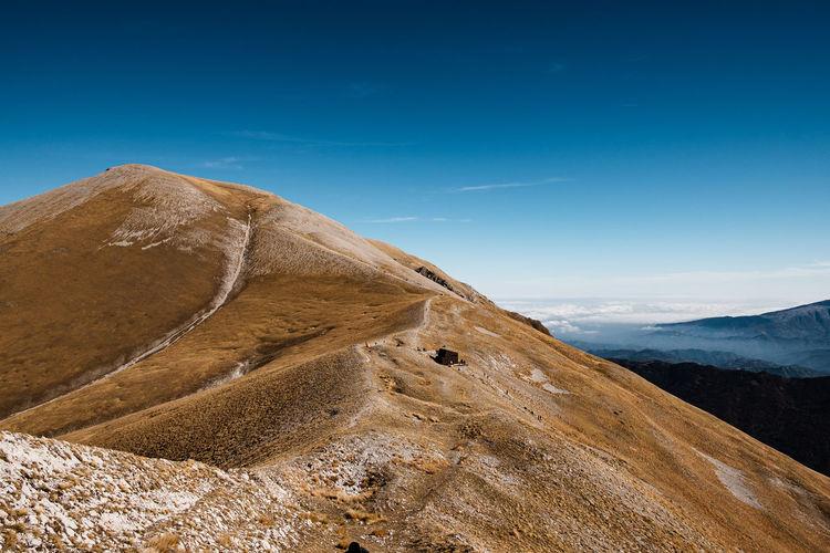 Scenic view of mountain against blue sky in arquata del tronto, marche italy