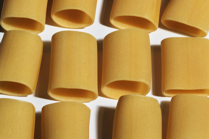 Three lines of pasta paccheri on a white background, the light direction highlighted the pasta shape ,top view ,golden yellow color Golden Lines Lunch Wheat Background Carbohydrates Columns Dry Geometric Gourmet Group Healthy Eating Italian Food No People Paccheri Pasta Raw Food Repeat Repetition Shadows Still Life Surface Traditional Uncooked Pasta Yellow Color