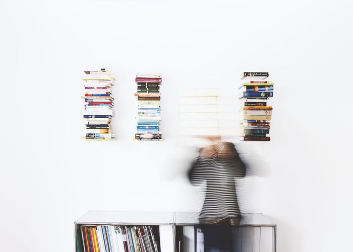 Stack of books on shelf against white background