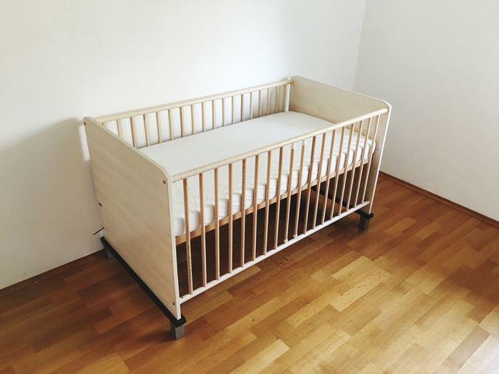 Empty crib on hardwood floor at home