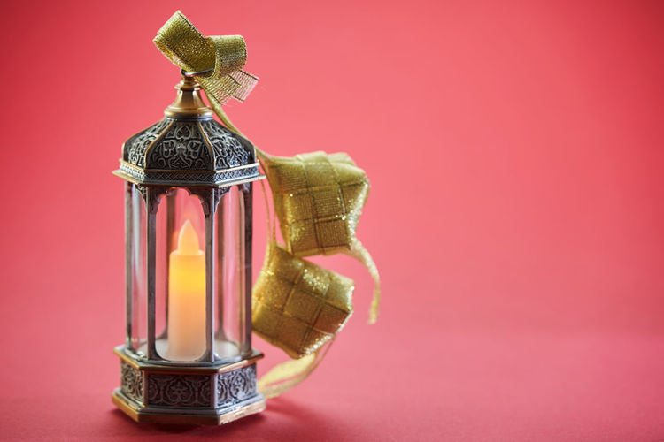 Close-up of electric lamp on red table against pink background