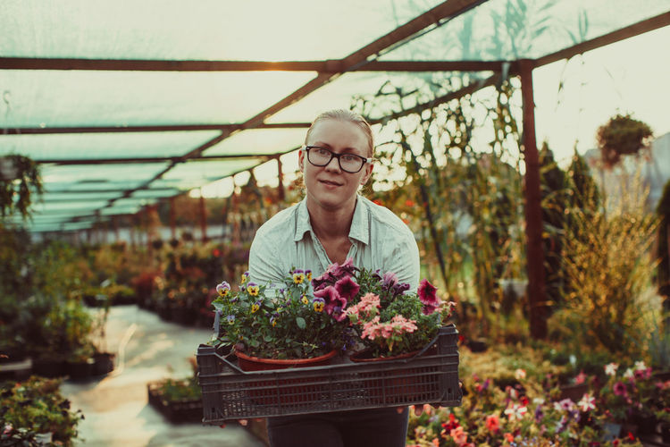 Portrait of smiling woman standing by plants at greenhouse