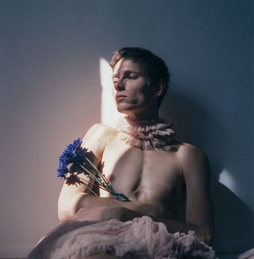 Shirtless young man with flowers sitting against wall