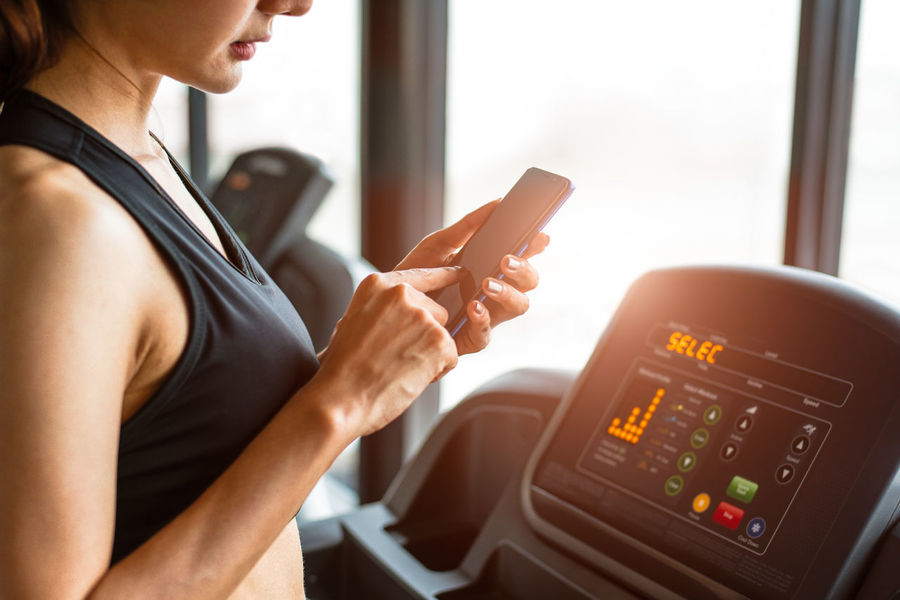 Woman using smart phone when workout or strength training at fitness gym on treadmill. Relax and Technology concept. Sports Exercise and Health care theme. Happy people and Comfortable application Treadmill Adult Applications  Calorie Calories Cardio Check Up Communication Connection Dieting Fitness Gym Healthy Indoors  Internet Jogging Lifestyles Look Up Measurement One Person Side View Technology Treadmills Wireless Technology Women